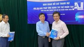 Ông Lê Quốc Cường, Phó Giám đốc Sở  TT-TT TPHCM (giữa) trao bài dự thi hội thi cho đại diện ban giám khảo