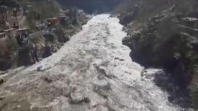 Một con đập bị dòng nước lũ hôm 7-2 đánh vào. Ảnh: REUTERS
