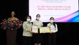 Đại diện Ủy ban MTTQ Việt Nam TPHCM tiếp nhận ủng hộ của Công ty JOY qua sự kết nối của Báo SGGP