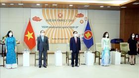 Bộ trưởng Bộ Ngoại giao Bùi Thanh Sơn và các đại biểu thực hiện nghi thức chào cờ ASEAN theo hình thức trực tuyến tại điểm cầu Hà Nội. Ảnh: TTXVN