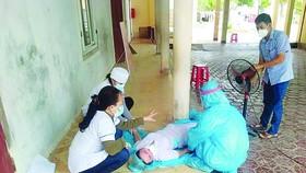 Các đồng nghiệp sơ cứu chị Nguyễn Thị Hương bị ngất xỉu. Ảnh: DƯƠNG QUANG