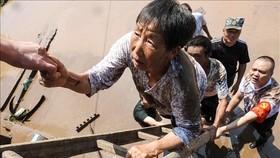 Nhân viên cứu hộ giúp sơ tán người dân khỏi các khu vực ngập lụt tại Dazhou, tỉnh Tứ Xuyên, Trung Quốc, ngày 12-7-2021. Ảnh: AFP/TTXVN