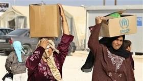 Người tị nạn Syria tại trại tị nạn Zaatari, thành phố Mafraq, Jordan, giáp biên giới Syria nhận hàng viện trợ của Liên hiệp quốc ngày 22-10-2012. Ảnh: REUTERS