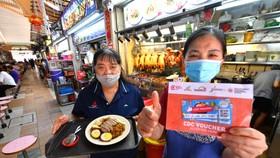 Người dân Singapore dùng phiếu thưởng e-voucher để mua hàng