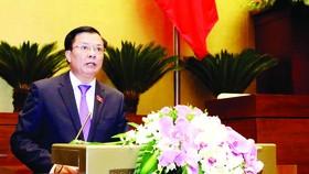 Bộ trưởng Bộ Tài chính Đinh Tiến Dũng trình bày báo cáo của Chính phủ tại kỳ họp. Ảnh: LÃ ANH