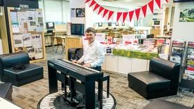 Tác giả và cây đàn dương cầm đặt trong thư viện trường quốc tế.