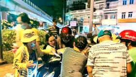 Trong vai người đi cho quà, sau chưa đầy 30 giây dừng xe, đám đông đi xin vây quanh và giật toàn bộ quà tặng trên xe PV Báo SGGP Ảnh: DŨNG PHƯƠNG