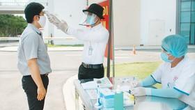 Người bệnh và người nhà bệnh nhân được  đo thân nhiệt, khai báo y tế ngay từ cổng bệnh viện Ảnh: MINH NAM