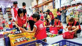Các tình nguyện viên ở Singapore chuẩn bị thực phẩm giúp đỡ người gặp khó khăn vì dịch bệnh.