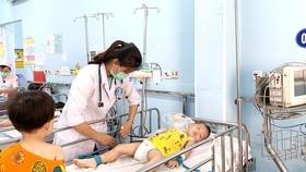Bác sĩ  Bệnh viện Nhi đồng 1 đang thăm khám và điều trị cho bệnh nhi mắc tay chân miệng Ảnh:  MINH NAM