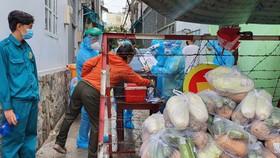 Lực lượng dân quân hỗ trợ chuyển lương thực giúp người dân ở quận Gò Vấp vào chiều 2-6  Ảnh: VĂN MINH