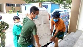 Vận chuyển các thiết bị y tế tại Bệnh viện dã chiến số 6. Ảnh: MINH NGHĨA