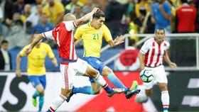 Roberto Firmino đi bóng qua hậu vệ Paraguay