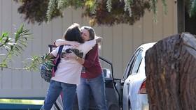 Phụ huynh động viên nhau bên ngoài ngôi trường (Ảnh : AP)