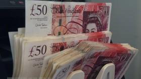Kiểm tiền bảng Anh. (Ảnh: AFP/TTXVN)