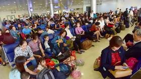 Hành khách vạ vật tại sân bay Tân Sơn Nhất, TP.HCM chờ đến giờ bay vào dịp tết - ẢNH: QUANG ĐỊNH