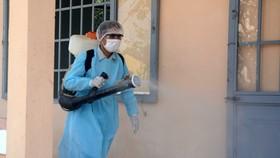 Nhân viên y tế thực hiện phun thuốc sát khuẩn tại Trung tâm Huấn luyện dự bị động viên Đồng Nghệ (xã Hòa Khương, huyện Hòa Vang, Đà Nẵng) đang thực hiện cách ly 69 người Việt Nam Daegu (Hàn Quốc) trở về. (Ảnh: Văn Dũng/TTXVN)