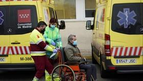 Các nhân viên y tế Tây Ban Nha di chuyển một bệnh nhân ở bệnh viện Octubre tại Madrid ngày 30-3 - Ảnh: REUTERS