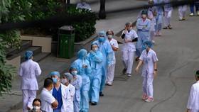 Cán bộ, y, bác sỹ Bệnh viện Bạch Mai xếp hàng chờ lấy mẫu xét nghiệm COVID-19. (Ảnh minh họa: Phạm Hùng/TTXVN phát)
