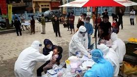 Lấy mẫu xét nghiệm cho người dân tại ổ dịch thôn Hạ Lôi. (Ảnh: Danh Lam/TTXVN)