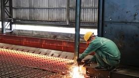 Công nhân Nhà máy cán thép Thái Trung (Công ty Cổ phần gang thép Thái Nguyên) lấy mẫu thép mới cán. (Ảnh: Hoàng Nguyên/TTXVN)