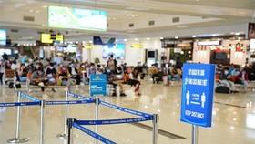 Chăng dây và biển thông báo để hành khách giữ khoảng cách tối thiểu 2m khi làm thủ tục hàng không. (Nguồn: TTXVN phát)