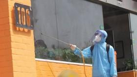 Nhân viên y tế phun khử khuẩn nhà hàng số 106, Trần Thái Tông. Ảnh: Tất Định