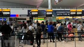 Công dân Việt Nam tại Anh xếp hàng chờ làm thủ tục lên máy bay về nước. (Ảnh: Đình Thư/TTXVN)