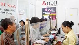 Khách hàng giao dịch vàng tại Công ty Doji. (Ảnh: Đức Duy/Vietnam+)