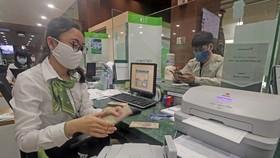 Khách hàng giao dịch tại hội sở chính Vietcombank, 198 Trần Quang Khải, Hà Nội. (Ảnh: Trần Việt/TTXVN)