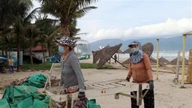 Người dân Đà Nẵng vận chuyển vật dụng kinh doanh trên các bãi biển đưa lên bờ để tránh thiệt hại khi bão số 9 đổ bộ. (Ảnh: Trần Lê Lâm/TTXVN)