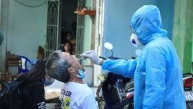 Nhân viên y tế lấy mẫu xét nghiệm người dân trong khu vực Lô E, Lò Gốm (Phường 7, Quận 6). (Ảnh: Đinh Hằng/TTXVN)
