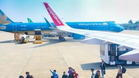 Hành khách đeo khẩu trang trước khi lên tàu bay tại Cảng hàng không Thọ Xuân, tỉnh Thanh Hóa. (Ảnh: Duy Khương/TTXVN)
