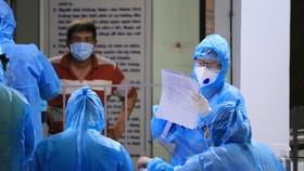 Nhân viên y tế thức trắng đêm xét nghiệm, kiểm tra tờ khai từ các nhân viên sân bay - Ảnh: NHẬT THỊNH