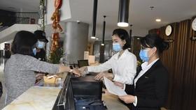 Nhân viên lễ tân khách sạn CAO Vũng Tàu đang tiến hành đo thân nhiệt cho du khách khi nhận phòng tại quầy lễ tân của khách sạn. (Ảnh: Ngọc Sơn/TTXVN)