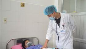 Bác sĩ chăm sóc cho bệnh nhân T. sau khi phẫu thuật thành công
