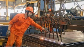 Công nhân lao động tại nhà xưởng Công ty cổ phần Cơ khí xây dựng thương mại Đại Dũng tại khu Công nghiệp An Hạ, huyện Bình Chánh. (Ảnh: Thanh Vũ/TTXVN)