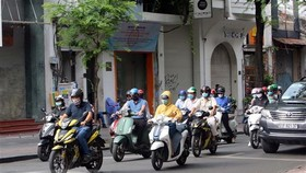 Người dân Thành phố Hồ Chí Minh thực hiện đeo khẩu trang phòng chống dịch COVID-19 khi tham gia giao thông. (Ảnh: Thanh Vũ/TTXVN)