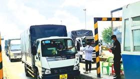 Kiểm tra các xe tải vận chuyển hàng hóa qua chốt Thân Cửu Nghĩa, tỉnh Tiền Giang. Ảnh: NGỌC PHÚC