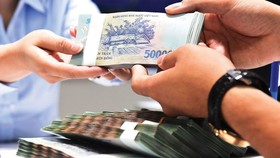 Ngân hàng giảm lãi suất vay vốn nhằm hỗ trợ doanh nghiệp ứng phó với dịch Covid-19. Ảnh minh họa: KT