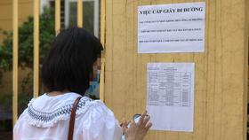 Đại diện một doanh nghiệp đến trụ sở Công an phường Dịch Vọng Hậu làm thủ tục cấp giấy đi đường - Ảnh: DANH TRỌNG