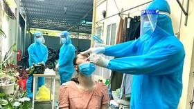 Lực lượng y tế lưu động phường 25, quận Bình Thạnh đến tận nơi điều trị cho người mắc Covid-19 tại phường. Ảnh: HOÀNG HÙNG