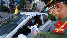 Lực lượng trực chốt cầu Vĩnh Tuy kiểm tra mã QR trên giấy đi đường của người dân sáng 8/9. (Ảnh: Hoàng Hiếu/TTXVN)