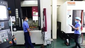 """Nhiều doanh nghiệp đề nghị có phương án thay thế """"3 tại chỗ"""". Trong ảnh: sản xuất tại một công ty ở quận 7 (TP.HCM) chuyên về khuôn mẫu và sản phẩm nhựa kỹ thuật cao - Ảnh: QUANG ĐỊNH"""
