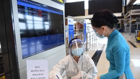 Hành khách kê khai bản cam kết phòng, chống dịch COIVD-19 tại sân bay Nội Bài - Ảnh: HOÀNG ANH
