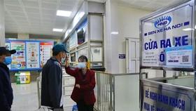 Nhân viên Bến xe Giáp Bát kiểm tra thân nhiệt tất cả hành khách vào bến. (Ảnh: Hoàng Hiếu/TTXVN)