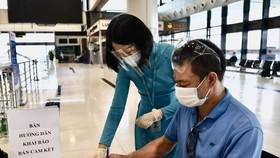 Hành khách đi máy bay làm thủ tục kê khai thông tin di chuyển nội địa để đảm bảo cho công tác phòng, chống dịch COVID-19. (Ảnh: CTV/Vietnam+)
