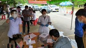 Nhân viên y tế làm nhiệm vụ kiểm tra sức khỏe người dân tại chốt kiểm soát ở Bình Dương