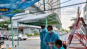 Lực lượng y tế làm nhiệm vụ truy vết các trường hợp tiếp xúc gần tại một chung cư ở TP Thuận An