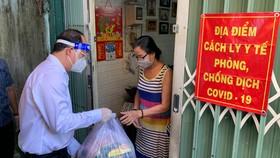 Phó Bí thư Thành ủy TPHCM Nguyễn Hồ Hải, tặng quà một người dân trong Khu phong tỏa tại một con hẻm trên đường Nơ Trang Long, P12, Q.Bình Thạnh. Ảnh: DŨNG PHƯƠNG